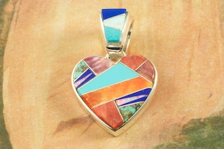 "Stunning Heart Pendant featuring Genuine Sleeping Beauty Turquoise, Blue Lapis and Spiny Oyster Shell inlaid between ribbons of Sterling Silver with Fire and Ice Lab Opal Accents. Free 18"" Sterling Silver Chain with Purchase of Pendant. Designed by Navajo Artist Artist Calvin Begay. Signed by the artist."
