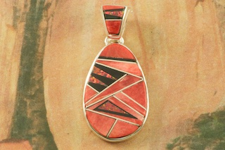 "Stunning Pendant features Genuine Fire Red Spiny Oyster Shell and Acoma Jet inlaid between ribbons of Sterling Silver. Accented with Fire Red Lab Opals. Free 18"" Sterling Silver Chain with Purchase of Pendant. Designed by Navajo Artist Calvin Begay. Signed by the artist."