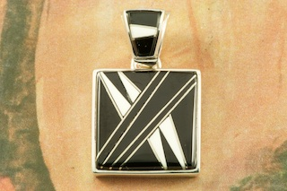 "Stunning Pendant featuring Genuine Acoma Jet and White Agate inlaid between ribbons of Sterling Silver. Free 18"" Sterling Silver Chain with Purchase of Pendant. Designed by Navajo Artist Calvin Begay. Signed by the artist."