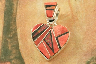 "Genuine Fire Red Spiny Oyster Shell and Acoma Jet inlaid between ribbons of Sterling Silver with  Fire Red Lab Opal Accents. Free 18"" Sterling Silver Chain with Purchase of Pendant. Designed by Navajo Artist Calvin Begay. Signed by the artist."
