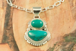 Genuine Royston Turquoise set in Sterling Silver Pendant. Created by Navajo Artist Sampson Jake. Signed by the artist. Free 18 inch Sterling Silver Chain with purchase of pendant. Royston Turquoise Mine was originally known as the Royal Blue Mine. It produces Turquoise that has a mixture of blues and greens in the same formation. The Royston Turquoise Mine is located in Nye County, Nevada.