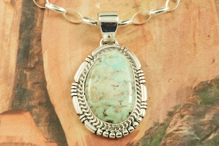 "Genuine Dry Creek Turquoise set in Sterling Silver Pendant. The Dry Creek mine is closed. It is now obtained from private collections. The Dry Creek Mine is located near Battle Mountain, Nevada. Dry Creek Turquoise forms when there are no heavy metals present such as copper or iron. To date, no other vein of this Turquoise has been discovered anywhere else other than the Dry Creek Mine and when this vein runs out, that will be the last of it. Because this Turquoise is as rare as the sacred buffalo, the Indians call it ""Sacred Buffalo Turquoise"". Created by Navajo Artist Sampson Jake. Signed by the artist. Free 18"" Sterling Silver Chain with Purchase of Pendant."