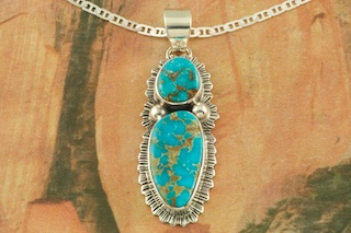 "Genuine Turquoise Mountain Mine Stones set in Sterling Silver Pendant. Free 18"" Sterling Silver Chain with Purchase of Pendant. Created by Navajo Artist Lyle Piaso. Signed by the artist. The Turquoise Mountain Mine is located in the Mineral Park Mining District, Mohave County, Arizona. Although Turquoise Mountain is located near the Kingman Turquoise Mine it is considered a classic mine in its own right because the Turquoise is so different in appearance. It is also known as ""Old Man Turquoise""."