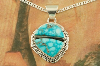 "Genuine Turquoise Mountain Mine Stones set in Sterling Silver Pendant. Free 18"" Sterling Silver Chain with Purchase of Pendant. Created by Navajo Artist Lucy Valencia. Signed L. J. by the artist. The Turquoise Mountain Mine is located in the Mineral Park Mining District, Mohave County, Arizona. Although Turquoise Mountain is located near the Kingman Turquoise Mine it is considered a classic mine in its own right because the Turquoise is so different in appearance. It is also known as ""Old Man Turquoise""."