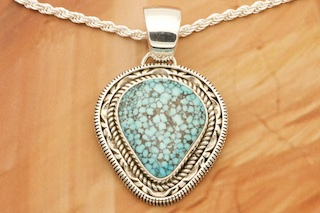 "Genuine High Grade Kingman Turquoise set in Sterling Silver Pendant. Created by Navajo Artist Artie Yellowhorse and Henry Chackee. Signed by the artist. The Mineral Park Mine, in the Cerbat Mountains 14 miles northwest of Kingman, was first mined by Indians centuries before white man came to the area. It is one of the three sites of prehistoric mining localities in the state of Arizona. Mineral Park was the most extensively worked area by the Indians of the three. S.A. ""Chuck"" Colbaugh found a cache of stone hammers uncovered in ancient trenches and tunnels, when he had the turquoise mining concession in May of 1962. Ithaca Peak and Turquoise Mine (formally called Aztec Mountain or Aztec Peak) are the most famous of the peaks in the area containing turquoise. Free 18"" Sterling Silver Chain with purchase of pendant."