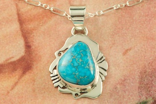 "Genuine High Grade Kingman Turquoise set in Sterling Silver Pendant. Created by Navajo Artist Herbert Pino. Signed by the artist. The Mineral Park Mine, in the Cerbat Mountains 14 miles northwest of Kingman, was first mined by Indians centuries before white man came to the area. It is one of the three sites of prehistoric mining localities in the state of Arizona. Mineral Park was the most extensively worked area by the Indians of the three. S.A. ""Chuck"" Colbaugh found a cache of stone hammers uncovered in ancient trenches and tunnels, when he had the turquoise mining concession in May of 1962. Ithaca Peak and Turquoise Mine (formally called Aztec Mountain or Aztec Peak) are the most famous of the peaks in the area containing turquoise. Free 18"" Sterling Silver Chain with purchase of pendant."