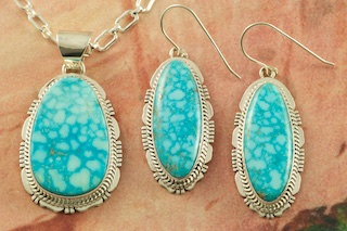 "Genuine Kingman Turquoise Stones set in Sterling Silver. Beautiful Pendant and Earrings Set with an 18"" Sterling Silver Chain. Created by Navajo Artist Lucy Valencia. Signed L. J. by the artist. The Mineral Park Mine, in the Cerbat Mountains 14 miles northwest of Kingman, was first mined by Indians centuries before white man came to the area. It is one of the three sites of prehistoric mining localities in the state of Arizona. Mineral Park was the most extensively worked area by the Indians of the three. S.A. ""Chuck"" Colbaugh found a cache of stone hammers uncovered in ancient trenches and tunnels, when he had the turquoise mining concession in May of 1962. Ithaca Peak and Turquoise Mine (formally called Aztec Mountain or Aztec Peak) are the most famous of the peaks in the area containing turquoise."