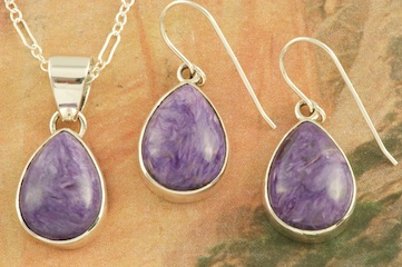 "Pendant and Earrings Set featuring Charoite set in Sterling Silver. Charoite is a Beautiful and interesting gemstone first introduced in the US around 1976. It's vivid colors range from lavender to deep chatoyant purple. It is mined in Siberia Russia near Charo River, Lake Baikal region. High grade charoite is distinguished by mixtures of deep rich purple and silky zones, in swirly and/or needle-like chatoyant patterns/sprays. Free 18"" Sterling Silver Chain with Purchase of Pendant. Created by Navajo ArtistLucy Valencia. Signed L. J. by the artist."