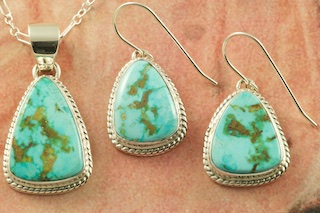 "Stunning Sterling Silver Pendant and Earrings set featuring Genuine Turquoise Mountain Mine Turquoise. Free 18"" Sterling Silver Chain with Purchase. Created by Navajo Artist Dale Livingston. Signed by the artist. The Turquoise Mountain Mine is located in the Mineral Park Mining District, Mohave County, Arizona. Although Turquoise Mountain is located near the Kingman Turquoise Mine it is considered a classic mine in its own right because the Turquoise is so different in appearance. It is also known as ""Old Man Turquoise""."