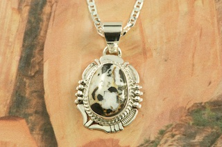 "Genuine White Buffalo Turquoise set in Sterling Silver Pendant. This Beautiful Stone is formed from the minerals Calcite and Iron. It is mined near Tonopah Nevada. Free 18"" Sterling Silver Chain with Purchase of Pendant. Created by Navajo Artist Bennie Ration. Signed by the artist."