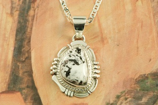 "Genuine White Buffalo Turquoise set in Sterling Silver Pendant. This Beautiful Stone is formed from the minerals Calcite and Iron. It is mined near Tonopah Nevada. Free 18"" Sterling Silver Chain with Purchase of Pendant. Created by Navajo Artist Larson Lee. Signed by the artist."