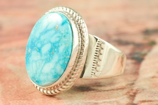 "Genuine Kingman Turquoise set in Sterling Silver Ring. Created by Navajo Artist Thomas Chischilly. Signed by the artist. The Mineral Park Mine, in the Cerbat Mountains 14 miles northwest of Kingman, was first mined by Indians centuries before white man came to the area. It is one of the three sites of prehistoric mining localities in the state of Arizona. Mineral Park was the most extensively worked area by the Indians of the three. S.A. ""Chuck"" Colbaugh found a cache of stone hammers uncovered in ancient trenches and tunnels, when he had the turquoise mining concession in May of 1962. Ithaca Peak and Turquoise Mine (formally called Aztec Mountain or Aztec Peak) are the most famous of the peaks in the area containing turquoise."