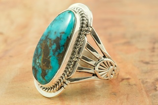 Genuine Apache Blue Turquoise set in Sterling Silver Ring. Created by Navajo Artist Lucy Valencia. Signed L. J. by the artist. The Apache Blue Mine turquoise mine, is a small mine with lots of potential. The mine is located near Tonopah, Nevada in the Candelaria Mountain range. In recent years the mine, (an open pit) has re-opened rendering Apache Blue turquoise with beautiful blue stones with eye popping black matrix. This high quality Apache turquoise is very rare and hard to find, even in this mine, but it's what every turquoise miner is searching for. Unfortunately only a small amount of this nice natural hard turquoise with really beautiful dark blue, webbed nuggets have been discovered. This turquoise is truly some of the nicest from Nevada.