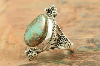"Beautiful Sterling Silver Ring featuring Pilot Mountain Turquoise. The Pilot Mountain Mine is located in western Nevada, east of the small town of Mina. Pilot Mountain turquoise forms in hard veins with color ranging from bright blue to dark blue with a greenish cast. Dark brown limonite mottled patterns are associated with this material. Most Pilot Mountain turquoise is called ""grass roots"", meaning the best deposits are found within ten feet of the surface. Created by Navajo Artist Lucy Valencia. Signed L. J. by the artist."