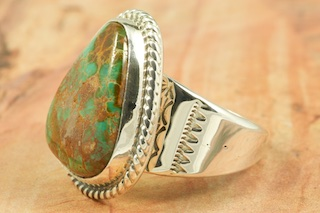 "Beautiful Sterling Silver Ring featuring Pilot Mountain Turquoise. The Pilot Mountain Mine is located in western Nevada, east of the small town of Mina. Pilot Mountain turquoise forms in hard veins with color ranging from bright blue to dark blue with a greenish cast. Dark brown limonite mottled patterns are associated with this material. Most Pilot Mountain turquoise is called ""grass roots"", meaning the best deposits are found within ten feet of the surface. Created by Navajo Artist Tony Garcia. Signed by the artist."