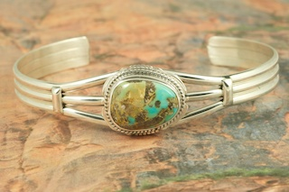 Genuine Candelaria Turquoise set in Sterling Silver Bracelet. Created by Navajo Artist Kathy Yazzie. Signed by the artist. Candelaria Turquoise comes from the large Candelaria Silver and Gold mine in Nevada in an area not to far from Tonopah. It is currently closed with no mining activity and as such Candelaria turquoise is rare and considered a collectable. The turquoise in this area was usually found in thin veins and is known for its beautiful almost electric blue stones, sometimes with a light matrix. Over the last few years Candelaria turquoise has been seen again in today�s turquoise market from older collections with beautiful dark blue stones with a beautiful matrix pattern and has now been cut and is appearing in fine jewelry. This mine produces some of the most unusual and beautiful patterns, no two stones are ever alike.