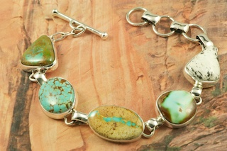Genuine Assorted Gemstones set in Sterling Silver Bracelet. Featuring Genuine Boulder Turquoise, Pilot Mountain Turquoise, White Buffalo Turquoise, Crow Springs Turquoise and Number 8 Mine Turquoise. The photo is of the jewelry you will be receiving. Created by Navajo Artist Tony Garcia. Signed by the artist.