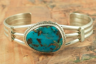 Stunning Bracelet featuring Genuine Apache Blue Turquoise set in heavy gauge Sterling Silver. Created by Navajo Artist Larson Lee. Signed by the artist. The Apache Blue Mine turquoise mine, is a small mine with lots of potential. The mine is located near Tonopah, Nevada in the Candelaria Mountain range. In recent years the mine, (an open pit) has re-opened rendering Apache Blue turquoise with beautiful blue stones with eye popping black matrix. This high quality Apache turquoise is very rare and hard to find, even in this mine, but it's what every turquoise miner is searching for. Unfortunately only a small amount of this nice natural hard turquoise with really beautiful dark blue, webbed nuggets have been discovered. This turquoise is truly some of the nicest from Nevada.