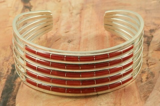 Stunning Bracelet featuring Genuine Red Coral inlaid between ribbons of  Sterling Silver. Created by Zuni Artists Anson and Letitica Wallace. Signed by the artist. The Zuni Pueblo is located in New Mexico, Land of Enchantment.