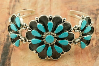 Genuine Sleeping Beauty Turquoise set in Sterling Silver Bracelet. Beautiful Flower Design. The Sleeping Beauty Turquoise mine is located in Gila County, Arizona. Created by Zuni Artist Delbert Booqua. Signed by the artist. The Zuni Pueblo is located in New Mexico, Land of Enchantment.