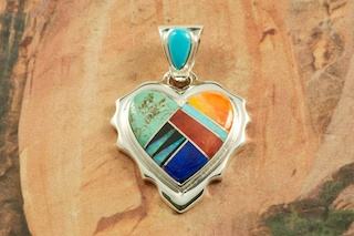 """Stunning Heart Pendant featuring Genuine Blue Lapis, Turquoise, Spiny Oyster Shell and Black Jade inlaid between ribbons of Sterling Silver. Precision inlay on the Bale and Pendant. Free 18"""" Sterling Silver Chain with Purchase of Pendant. Created by Navajo Artist Rick Tolino. Signed by the artist."""