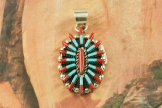 "Beautiful Needle Point Design with Genuine Sleeping Beauty Turquoise and Red Coral set in Sterling Silver Pendant. Created by Zuni Artist Carla Lonconsello. Signed by the artist. Free 18"" Sterling Silver Chain with Purchase of Pendant. The Zuni Pueblo is located in New Mexico, Land of Enchantment."