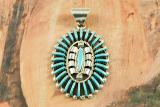 "Genuine Sleeping Beauty Turquoise set in Sterling Silver Pendant. Beautiful Needle Point Design. The Sleeping Beauty Turquoise Mine is located in Gila County, Arizona. Free 18"" Sterling Silver Chain with Purchase of Pendant. Created by Zuni Artist Edmund Cooeyate. Signed by the artist. The Zuni Pueblo is located in New Mexico, Land of Enchantment."
