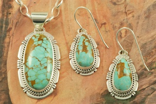 "Genuine Number 8 Mine Turquoise Stones set in Sterling Silver. Beautiful Pendant and Earrings Set with an 18"" Sterling Silver Chain. Created by Navajo Artist Sampson Jake. Signed by the artist. The Number 8 mine is located in Eureka County Nevada. Since 1976 there has been no Number 8 Turquoise mined. There is however, an existing stock pile that Mr. Dowell Ward, the last owner of the Number 8 mine, had stocked away for later sorting. The Turquoise is a collector's item--because once the reserve is gone there will be no more material released onto the market. The Gold Mining Company owns the claim to the Number 8 mine and it has been swallowed up by the gold mining operations. This is some of the last Number 8 Turquoise to be had and will be a great addition to your collection."
