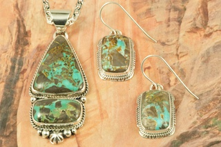 Stunning Pendant and Earrings Set featuring Genuine Candelaria Turquoise set in Sterling Silver. Created by Navajo Artists Larson Lee and Lucy Valencia. Signed by the artist. Candelaria Turquoise comes from the large Candelaria Silver and Gold mine in Nevada in an area not to far from Tonopah. It is currently closed with no mining activity and as such Candelaria turquoise is rare and considered a collectable. The turquoise in this area was usually found in thin veins and is known for its beautiful almost electric blue stones, sometimes with a light matrix. Over the last few years Candelaria turquoise has been seen again in today�s turquoise market from older collections with beautiful dark blue stones with a beautiful matrix pattern and has now been cut and is appearing in fine jewelry. This mine produces some of the most unusual and beautiful patterns, no two stones are ever alike.