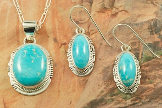 "Genuine Sleeping Beauty Turquoise set in Sterling Silver. Beautiful Pendant and Earrings Set with an 18"" Sterling Silver Chain. Created by Navajo Artist Lucy Valencia. Signed L. J. by the artist. The Sleeping Beauty Turquoise mine is located in Gila County, Arizona. The Sleeping Beauty Turquoise Mine is now closed. The stones are obtained from private collections."