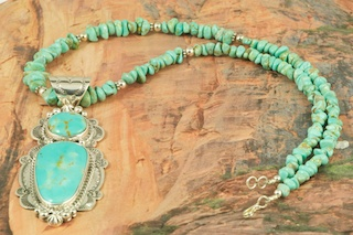Stunning Pendant and Necklace Set. Genuine Pilot Mountain Turquoise set in Sterling Silver Pendant. Necklace features Genuine Number 8 Mine Turquoise with Sterling Silver Beads and Clasp. Created by Navajo Artist Freddy Charley. Signed by the artist. The Pilot Mountain mine is located in Esmeralda County, Nevada.The Pilot Mountain Mine is located in Esmeralda County, Nevada. Pilot Mountain turquoise was first mined around 1930 as a tunnel mine. Then it became an open pit mine when heavy equipment was available around 1970. The current owners of the claim have been mining the turquoise since 1989. While Pilot Mountain is considered an active mine, it is a very small operation. The miners go to the mine twice per year, bringing out only about 150 to 200 lbs. of rough stone each time. One of the current owners says one of the interesting parts of mining is �not knowing what you are going to hit next.�