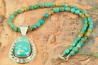 Stunning Pendant and Necklace Set. Genuine Pilot Mountain Turquoise set in Sterling Silver Pendant. Necklace features Genuine Turquoise with Sterling Silver Beads and Clasp. Created by Navajo Artist Jimmy Secatero. Signed by the artist. The Pilot Mountain mine is located in Esmeralda County, Nevada.The Pilot Mountain Mine is located in Esmeralda County, Nevada. Pilot Mountain turquoise was first mined around 1930 as a tunnel mine. Then it became an open pit mine when heavy equipment was available around 1970. The current owners of the claim have been mining the turquoise since 1989. While Pilot Mountain is considered an active mine, it is a very small operation. The miners go to the mine twice per year, bringing out only about 150 to 200 lbs. of rough stone each time. One of the current owners says one of the interesting parts of mining is �not knowing what you are going to hit next.�