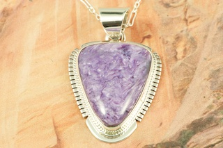 "Genuine Charoite set in Sterling Silver Pendant. Charoite is a Beautiful and interesting gemstone first introduced in the US around 1976. It's vivid colors range from lavender to deep chatoyant purple. It is mined in Siberia Russia near Charo River, Lake Baikal region. High grade charoite is distinguished by mixtures of deep rich purple and silky zones, in swirly and/or needle-like chatoyant patterns/sprays. Free 18"" Sterling Silver Chain with Purchase of Pendant. Created by Navajo Artist Kathy Yazzie. Signed by the artist."
