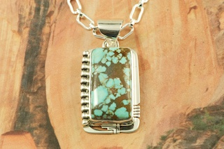 "Genuine Number 8 Mine Turquoise Stone set in Sterling Silver Pendant. Free 18"" Sterling Silver Chain with Purchase of Pendant. Created by Navajo Artist Phillip Sanchez. Signed by the artist. The Number 8 mine is located in Eureka County Nevada. Since 1976 there has been no Number 8 Turquoise mined. There is however, an existing stock pile that Mr. Dowell Ward, the last owner of the Number 8 mine, had stocked away for later sorting. The Turquoise is a collector's item--because once the reserve is gone there will be no more material released onto the market. The Gold Mining Company owns the claim to the Number 8 mine and it has been swallowed up by the gold mining operations. This is some of the last Number 8 Turquoise to be had and will be a great addition to your collection."