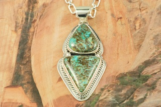 Genuine Sunnyside Turquoise set in Sterling Silver Pendant. Created by Navajo Artist Jake Sampson. Signed by the artist. The matrix on this rare stone is outstanding. The Sunnyside mine is located in northern Nevada near the town of Tuscarora in the Tuscarora mountain range.The mine is no longer in operation as it has become part of a gold mining operation and a privately owned ranch. The Sunnyside mine was mined mostly in the 70's. You won't find much of this great turquoise around anymore except for old stashes. Free 18 inch Sterling Silver Chain with purchase of pendant.