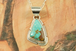 """Genuine Number 8 Mine Turquoise Stone set in Sterling Silver Pendant. Free 18"""" Sterling Silver Chain with Purchase of Pendant. Created by Navajo Artist Kathy Yazzie. Signed by the artist. The Number 8 mine is located in Eureka County Nevada. Since 1976 there has been no Number 8 Turquoise mined. There is however, an existing stock pile that Mr. Dowell Ward, the last owner of the Number 8 mine, had stocked away for later sorting. The Turquoise is a collector's item--because once the reserve is gone there will be no more material released onto the market. The Gold Mining Company owns the claim to the Number 8 mine and it has been swallowed up by the gold mining operations. This is some of the last Number 8 Turquoise to be had and will be a great addition to your collection."""