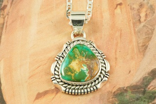 "Stunning Pendant featuring Genuine Pilot Mountain Turquoise set in Sterling Silver. Free 18 inch Sterling Silver Chain with purchase of pendant. The Pilot Mountain Mine is located in western Nevada, east of the small town of Mina. Pilot Mountain turquoise forms in hard veins with color ranging from bright blue to dark blue with a greenish cast. Dark brown limonite mottled patterns are associated with this material. Most Pilot Mountain turquoise is called ""grass roots"", meaning the best deposits are found within ten feet of the surface. Created by Navajo Artist Walter Vandever. Signed by the artist."