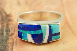 Stunning Ring featuring Genuine Turquoise, Blue Lapis and Magnesite inlaid in Sterling Silver. Fire and Ice Lab Opal Accents. Designed by Navajo Artist Calvin Begay. Signed by the artist.