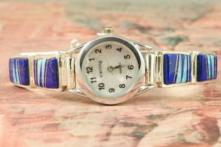 Quartz Watch Bracelet featuring Genuine Blue Lapis with accents of Fire and Ice Lab Opals inlaid between ribbons of Sterling Silver. Created by Navajo Artist Calvin Begay. Signed by the artist.