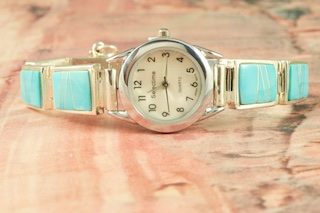 Quartz Watch Bracelet featuring Genuine Sleeping Beauty Turquoise inlaid between ribbons of Sterling Silver. Created by Navajo Artist Calvin Begay. Signed by the artist.